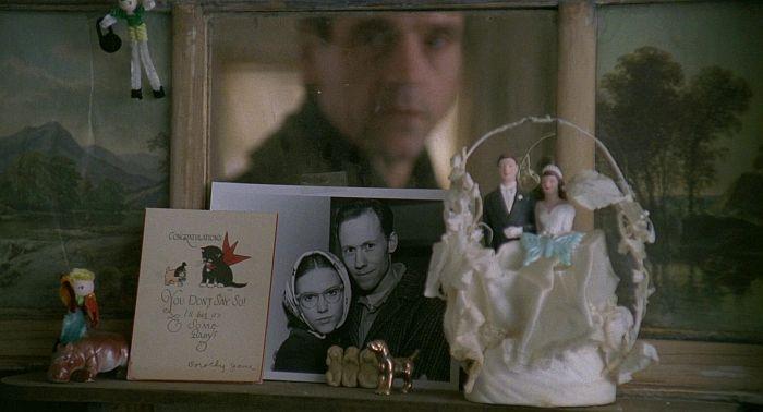 Джереми Айронс в роли Гумберта (в отражении) рассматривает семейное фото Лолиты. Статуэтка трех обезьян перед фото. Кадр из фильма «Лолита» 1997 г. режиссера Эдриана Лайна